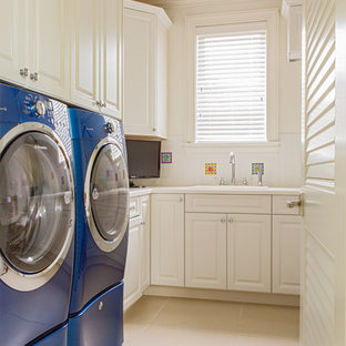 Example of a large classic l-shaped porcelain tile dedicated laundry room design in Miami with a drop-in sink, raised-panel cabinets, white cabinets, solid surface countertops, white walls and a side-by-side washer/dryer