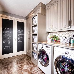 Bild på en stor vintage parallell tvättstuga enbart för tvätt, med grå skåp, granitbänkskiva, grå väggar, klinkergolv i porslin, en tvättmaskin och torktumlare bredvid varandra och luckor med upphöjd panel