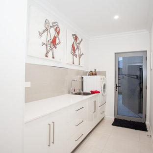 Foto på en mellanstor funkis vita linjär tvättstuga enbart för tvätt, med en enkel diskho, vita skåp, vita väggar, släta luckor, granitbänkskiva, beige stänkskydd, stänkskydd i keramik, klinkergolv i keramik och vitt golv