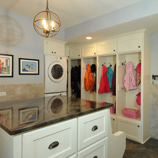 Example of a large transitional ceramic floor utility room design in Chicago with recessed-panel cabinets, white cabinets, quartzite countertops, blue walls and a stacked washer/dryer