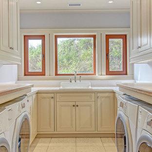 Immagine di una grande lavanderia stile americano con lavello stile country, ante in stile shaker, ante bianche, top piastrellato, pareti bianche, pavimento in gres porcellanato, lavatrice e asciugatrice affiancate e pavimento bianco