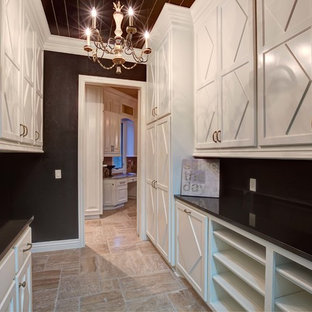 Photo of a large classic galley separated utility room in Oklahoma City with shaker cabinets, white cabinets, composite countertops, black walls, limestone flooring and a side by side washer and dryer.