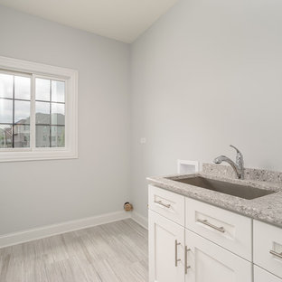 Design ideas for a mid-sized transitional single-wall dedicated laundry room in Chicago with an undermount sink, recessed-panel cabinets, white cabinets, terrazzo benchtops, grey walls, light hardwood floors, a side-by-side washer and dryer, grey floor and grey benchtop.