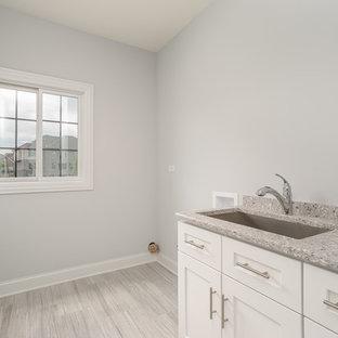 Inredning av en klassisk mellanstor grå linjär grått tvättstuga enbart för tvätt, med en undermonterad diskho, luckor med infälld panel, vita skåp, bänkskiva i terrazo, grå väggar, ljust trägolv, en tvättmaskin och torktumlare bredvid varandra och grått golv