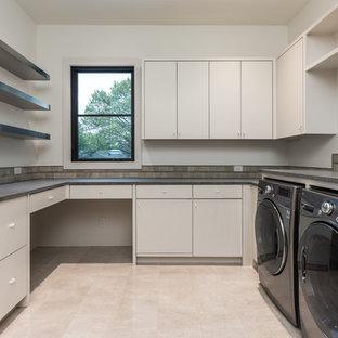 Ispirazione per una sala lavanderia minimalista di medie dimensioni con lavello sottopiano, ante lisce, ante bianche, top in cemento, pareti bianche, pavimento in cemento, lavatrice e asciugatrice affiancate, pavimento bianco e top grigio
