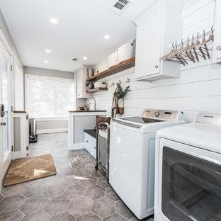 Idéer för att renovera en stor lantlig linjär tvättstuga enbart för tvätt, med skåp i shakerstil, vita skåp, granitbänkskiva, klinkergolv i keramik, en tvättmaskin och torktumlare bredvid varandra, grått golv och grå väggar