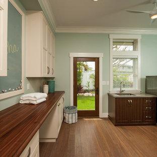 Idéer för mellanstora vintage grovkök, med en undermonterad diskho, vita skåp, träbänkskiva, gröna väggar, bambugolv, en tvättmaskin och torktumlare bredvid varandra och luckor med infälld panel