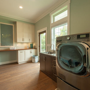 Foto di una lavanderia multiuso chic di medie dimensioni con lavello sottopiano, ante bianche, top in legno, pareti verdi, pavimento in bambù e lavatrice e asciugatrice affiancate
