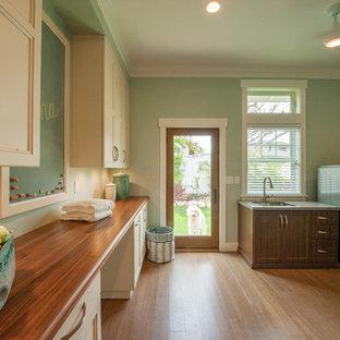 Ispirazione per una lavanderia multiuso classica di medie dimensioni con lavello sottopiano, ante bianche, top in legno, pareti verdi, pavimento in bambù, lavatrice e asciugatrice affiancate e ante con riquadro incassato