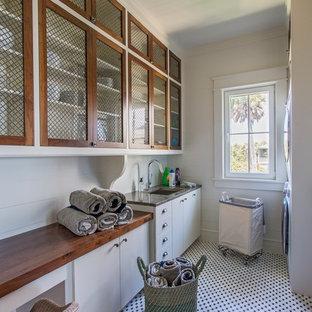 Inredning av en exotisk stor bruna parallell brunt tvättstuga enbart för tvätt, med en undermonterad diskho, vita skåp, träbänkskiva, vita väggar och en tvättpelare