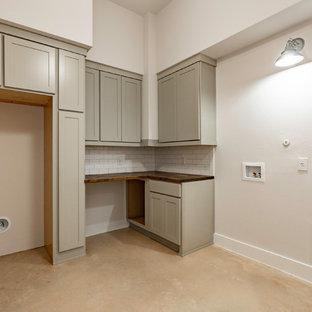 Esempio di una sala lavanderia country di medie dimensioni con ante con riquadro incassato, ante grigie, top in legno, pareti beige, pavimento in cemento, lavatrice e asciugatrice a colonna, pavimento grigio e top marrone