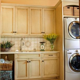 Esempio di una sala lavanderia mediterranea di medie dimensioni con lavello sottopiano, ante con riquadro incassato, ante in legno chiaro, top in quarzo composito, moquette, lavatrice e asciugatrice a colonna, pavimento beige, top beige e pareti beige