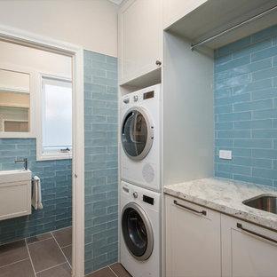Foto di una piccola lavanderia multiuso chic con lavello sottopiano, ante in stile shaker, ante beige, top in granito, pavimento in gres porcellanato, lavatrice e asciugatrice a colonna, pavimento grigio, pareti beige e top beige