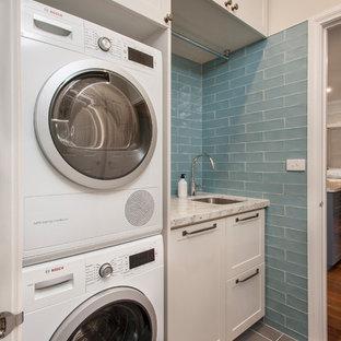 Bild på en liten vintage vita linjär vitt tvättstuga enbart för tvätt, med en undermonterad diskho, skåp i shakerstil, beige skåp, granitbänkskiva, blå väggar, klinkergolv i porslin, en tvättpelare och grått golv