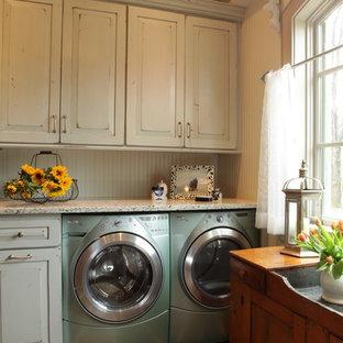 Idéer för att renovera ett stort vintage grovkök, med vita skåp, luckor med upphöjd panel, granitbänkskiva, beige väggar, skiffergolv och en tvättmaskin och torktumlare bredvid varandra