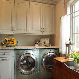 Inspiration for a large classic utility room in St Louis with white cabinets, raised-panel cabinets, granite worktops, beige walls, slate flooring and a side by side washer and dryer.