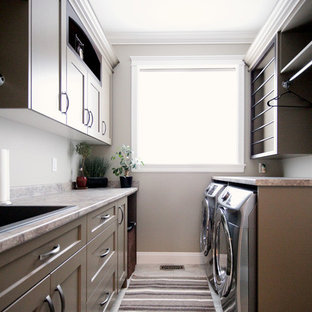 Inspiration for a mid-sized timeless galley porcelain floor dedicated laundry room remodel in Vancouver with a drop-in sink, shaker cabinets, brown cabinets, laminate countertops, gray walls and a side-by-side washer/dryer
