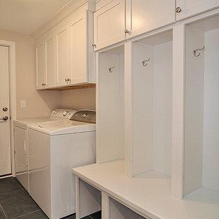 Foto på ett mellanstort amerikanskt grovkök, med skåp i shakerstil, vita skåp, träbänkskiva, klinkergolv i porslin och en tvättmaskin och torktumlare bredvid varandra