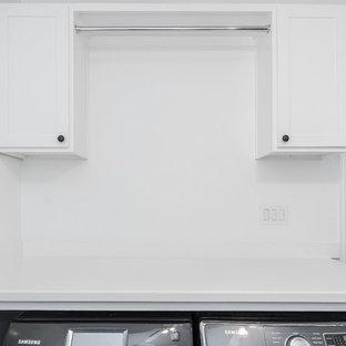 Foto di una lavanderia country di medie dimensioni con lavello stile country, ante in stile shaker, ante bianche, top in quarzo composito, paraspruzzi blu, paraspruzzi con piastrelle di vetro, pavimento in gres porcellanato, pavimento grigio e top bianco