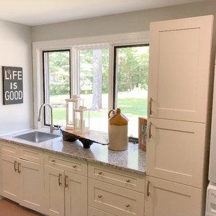 Foto di una sala lavanderia stile americano di medie dimensioni con lavello sottopiano, ante con riquadro incassato, ante bianche, top in laminato, pareti grigie, pavimento in laminato, lavatrice e asciugatrice a colonna, pavimento marrone e top grigio