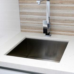 Exempel på ett mellanstort modernt vit linjärt vitt grovkök, med en undermonterad diskho, släta luckor, bänkskiva i kvarts, vitt stänkskydd, glaspanel som stänkskydd, mörkt trägolv, vita skåp, brunt golv, tvättmaskin och torktumlare byggt in i ett skåp och vita väggar