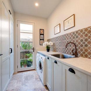 Idéer för en liten medelhavsstil parallell tvättstuga enbart för tvätt, med en nedsänkt diskho, skåp i shakerstil, vita skåp, vita väggar, travertin golv, en tvättmaskin och torktumlare bredvid varandra och laminatbänkskiva