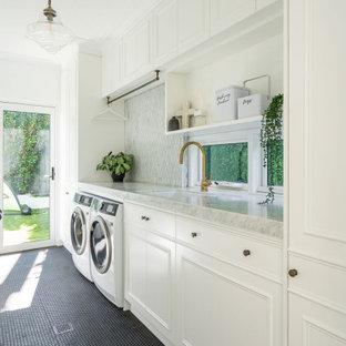 Inspiration för en vintage grå linjär grått tvättstuga, med en undermonterad diskho, luckor med infälld panel, vita skåp, vita väggar, en tvättmaskin och torktumlare bredvid varandra och svart golv
