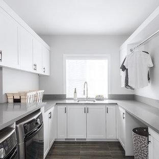 Mid-sized contemporary single-wall utility room in Toronto with an undermount sink, shaker cabinets, white cabinets, solid surface benchtops, porcelain floors, a side-by-side washer and dryer, brown floor, grey benchtop and white walls.