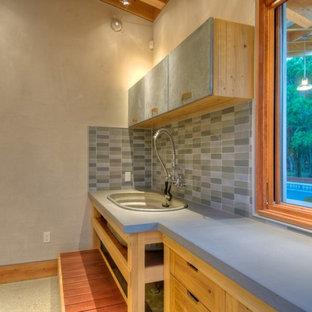 Exemple d'une buanderie parallèle nature dédiée et de taille moyenne avec un plan de travail en béton, béton au sol, un évier utilitaire, un placard à porte plane, des portes de placard en bois brun et un plan de travail gris.