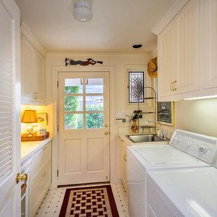 Idéer för en mellanstor amerikansk parallell tvättstuga enbart för tvätt, med en nedsänkt diskho, skåp i shakerstil, vita skåp, bänkskiva i kvarts, vita väggar, linoleumgolv och en tvättmaskin och torktumlare bredvid varandra