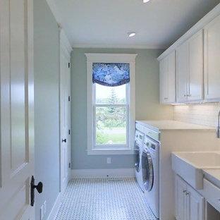 Inredning av en klassisk parallell tvättstuga enbart för tvätt, med en rustik diskho, vita skåp, marmorbänkskiva, gröna väggar, marmorgolv och en tvättmaskin och torktumlare bredvid varandra