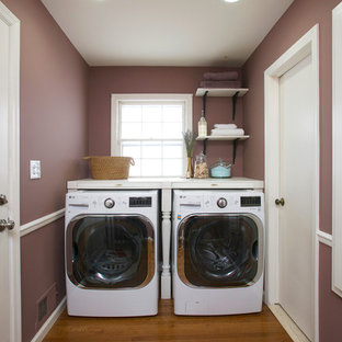 Small transitional single-wall dedicated laundry room in New York with wood benchtops, purple walls, medium hardwood floors and a side-by-side washer and dryer.