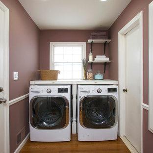Exempel på en liten klassisk linjär tvättstuga enbart för tvätt, med träbänkskiva, lila väggar, mellanmörkt trägolv och en tvättmaskin och torktumlare bredvid varandra