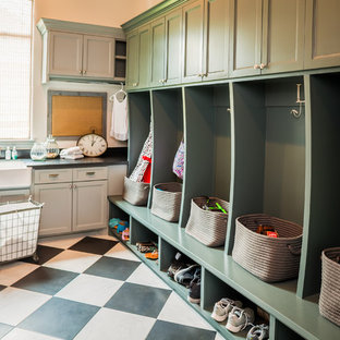 Example of a classic l-shaped linoleum floor and multicolored floor utility room design in Houston with a farmhouse sink, green cabinets, white walls, a side-by-side washer/dryer and recessed-panel cabinets