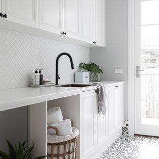 Klassisk inredning av en mellanstor vita parallell vitt tvättstuga enbart för tvätt, med en enkel diskho, skåp i shakerstil, vita skåp, bänkskiva i kvarts, vitt stänkskydd, stänkskydd i mosaik, grå väggar, klinkergolv i porslin, en tvättmaskin och torktumlare bredvid varandra och flerfärgat golv
