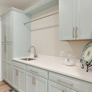 Large contemporary l-shaped separated utility room in Atlanta with a submerged sink, shaker cabinets, engineered stone countertops, porcelain flooring and a stacked washer and dryer.