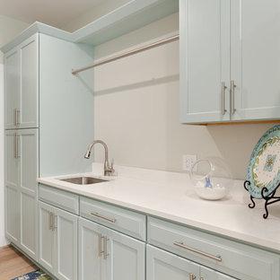 Ispirazione per una grande sala lavanderia design con lavello sottopiano, ante in stile shaker, top in quarzo composito, pavimento in gres porcellanato e lavatrice e asciugatrice a colonna