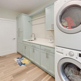 Foto på en stor funkis vita linjär tvättstuga enbart för tvätt, med en undermonterad diskho, skåp i shakerstil, bänkskiva i kvarts, klinkergolv i porslin, en tvättpelare, blå skåp, vita väggar och beiget golv
