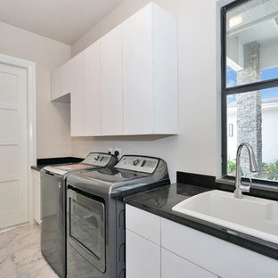 Design ideas for a medium sized contemporary single-wall separated utility room in Miami with a built-in sink, flat-panel cabinets, white cabinets, granite worktops, beige walls, marble flooring, a side by side washer and dryer, white floors and black worktops.