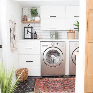トロントの小さいモダンスタイルのおしゃれな洗濯室 (アンダーカウンターシンク、フラットパネル扉のキャビネット、白いキャビネット、クオーツストーンカウンター、白い壁、セラミックタイルの床、左右配置の洗濯機・乾燥機、黒い床) の写真