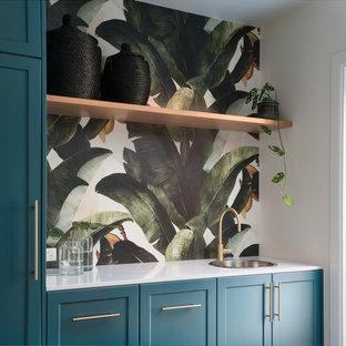Ispirazione per una lavanderia multiuso chic di medie dimensioni con lavello da incasso, ante in stile shaker, top in quarzo composito, pareti bianche, parquet scuro, lavatrice e asciugatrice nascoste, pavimento marrone, top bianco e ante blu