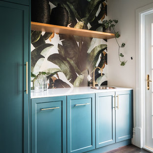Inredning av ett klassiskt mellanstort vit parallellt vitt grovkök, med en nedsänkt diskho, skåp i shakerstil, bänkskiva i kvarts, vita väggar, mörkt trägolv, tvättmaskin och torktumlare byggt in i ett skåp, brunt golv och blå skåp