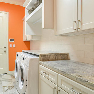 Design ideas for a large classic u-shaped utility room in Tampa with a built-in sink, flat-panel cabinets, white cabinets, granite worktops, orange walls, marble flooring and a side by side washer and dryer.