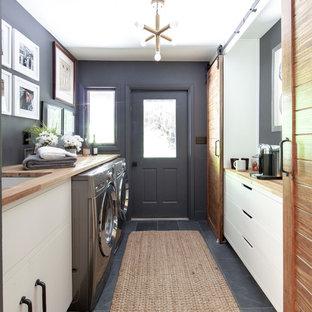 Exemple d'une buanderie nature avec un évier encastré, un placard à porte plane, un plan de travail en bois, un mur gris, des machines côte à côte, un sol gris, un plan de travail beige, un sol en ardoise et des portes de placard blanches.