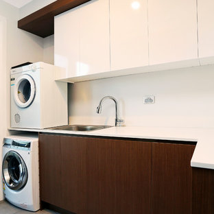 Inspiration for a large contemporary l-shaped dedicated laundry room in Sydney with flat-panel cabinets, white cabinets, quartz benchtops, metallic splashback, mirror splashback, porcelain floors, grey floor, white benchtop, a drop-in sink, white walls and a stacked washer and dryer.