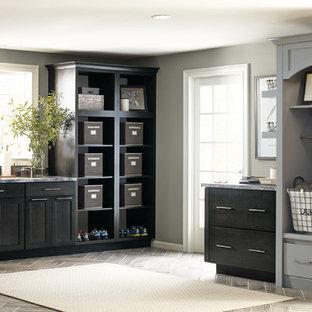 Cette photo montre une grand buanderie chic en L multi-usage avec un évier intégré, un placard à porte shaker, des portes de placard grises, un mur gris, des machines côte à côte et un plan de travail gris.