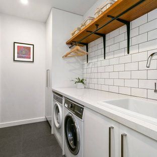 Contemporary galley dedicated laundry room in Sydney with white cabinets, quartz benchtops, white walls, porcelain floors, a side-by-side washer and dryer, grey floor, white benchtop, a drop-in sink and flat-panel cabinets.