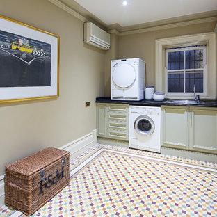 Klassisk inredning av en linjär tvättstuga enbart för tvätt, med en enkel diskho, beige skåp, bänkskiva i onyx, beige väggar, klinkergolv i keramik, en tvättpelare och luckor med infälld panel