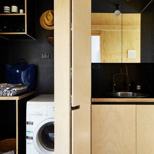Пример оригинального дизайна: маленькая прямая универсальная комната в стиле лофт с светлыми деревянными фасадами, столешницей из ламината, черными стенами, бетонным полом, накладной раковиной, фасадами с утопленной филенкой, со скрытой стиральной машиной и серым полом