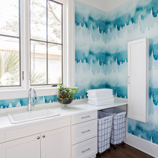 Beach style single-wall dedicated laundry room in Charleston with a drop-in sink, shaker cabinets, white cabinets, blue walls, dark hardwood floors, brown floor, white benchtop and wallpaper.